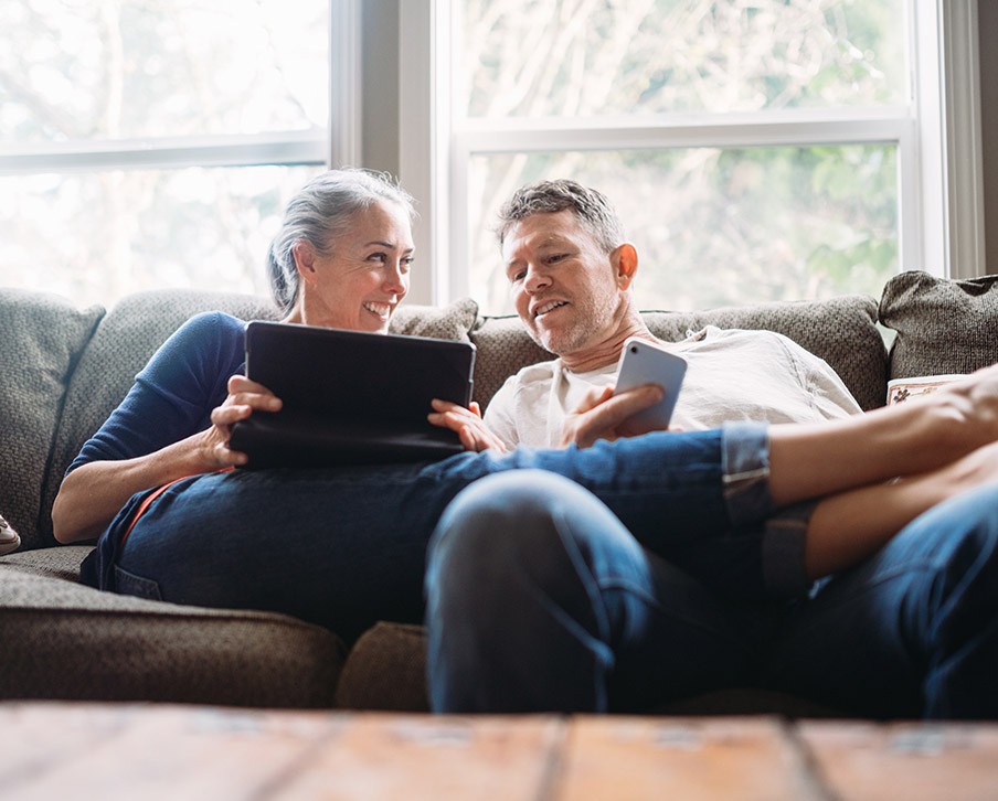 Happy looking man and woman on a sofa